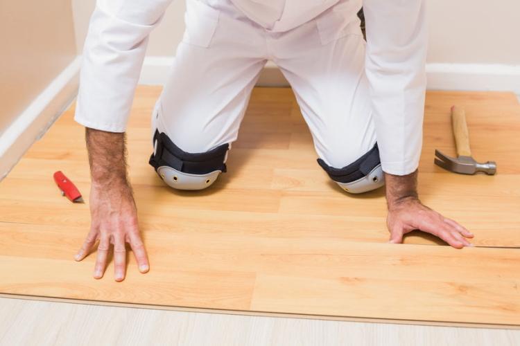 Carpenter Wearing Knee Pads Fixing Floor